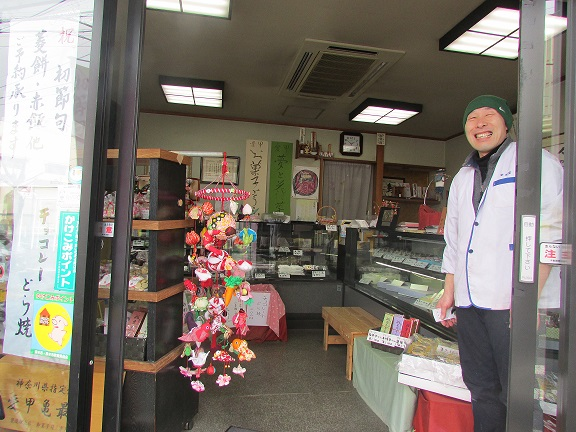 幸月堂さんは、愛甲石田駅南口のすぐ前にあります。メイサムホールには移動販売にも来ていただいています。写真はつるし雛とご主人の浅井さんです。